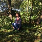 in der Natur sitzende Frau